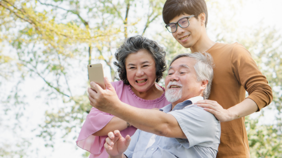 A senior couple and their grandson take photos outdoors together