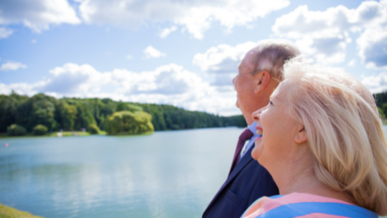 A senior couple stands at a lake and looks up at the clouds