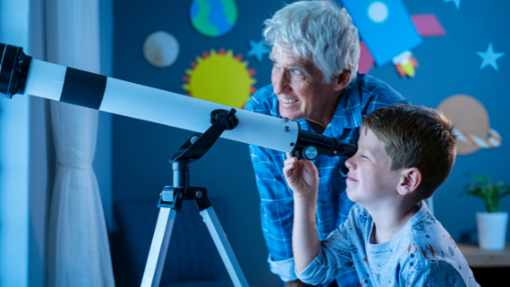 A grandpa and grandson use a telescope to look at the stars from the grandson's bedroom