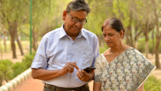 An elderly Indian couple go for a guided walk with their cell phone