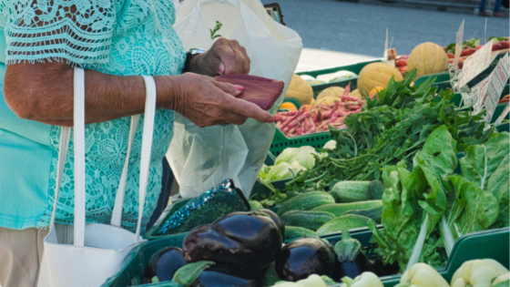 Close up of a senior woman purchasing produce at a farmer's market