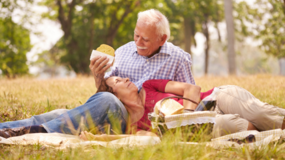 A loving senior couple enjoy a spring picnic outdoors