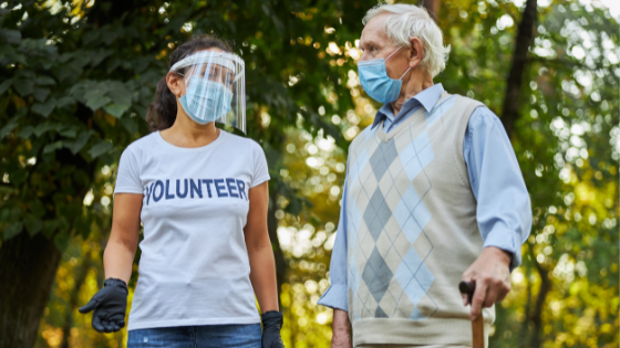 A senior man volunteers outdoors with a volunteer group while wearing a mask