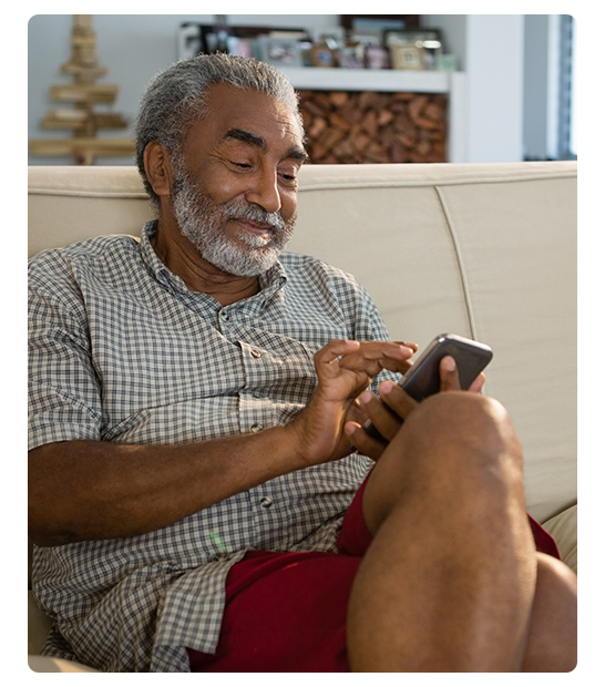 Senior man sits on his couch while texting on his phone