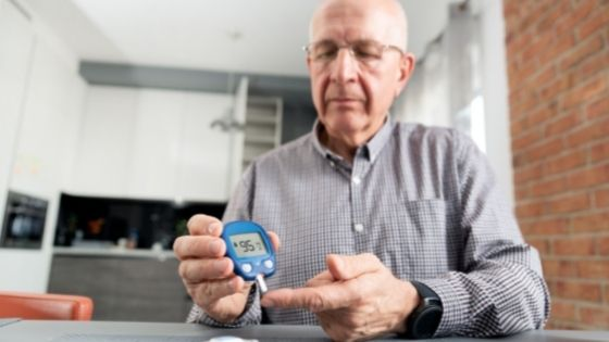 A man is seen testing his blood sugar levels in his kitchen