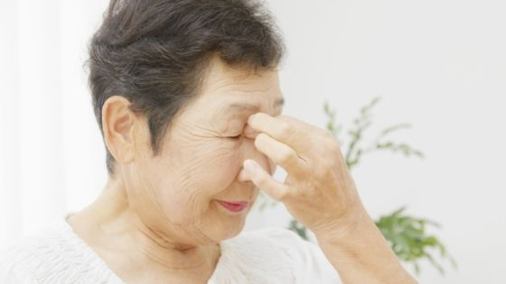 A senior woman pinches her forehead in pain