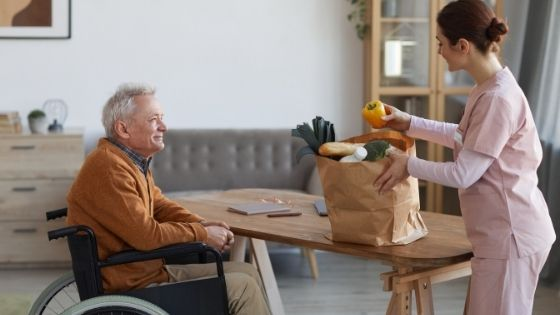 A female caregiver bings in groceries for a senior man in a wheelchair