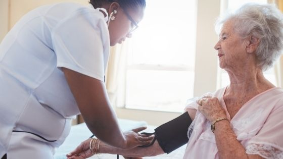 A female caregiver is seen checking the blood pressure of a senior woman