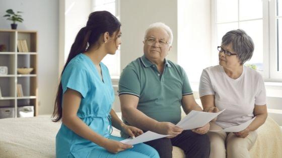 A senior couple discuss paperwork with a caregiver