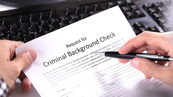 Close up of a person reviewing a paper background check request form