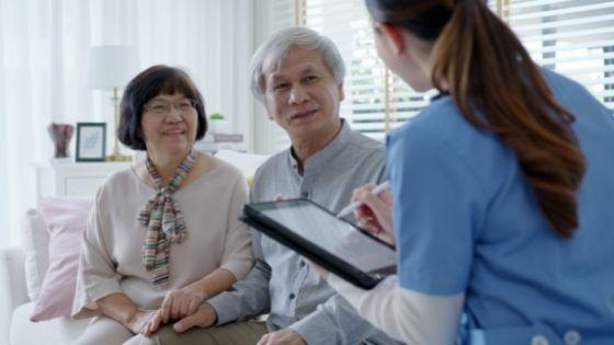 A female caregiver reviews a care plan with a senior couple