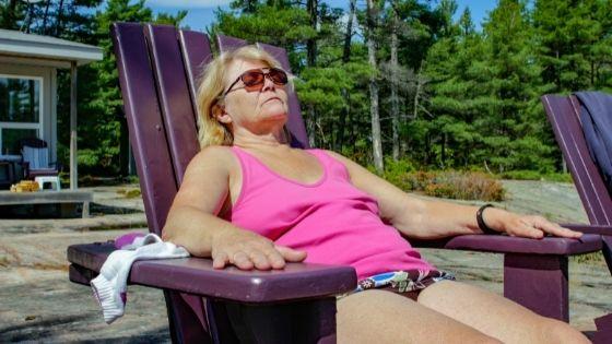 A senior woman is seen sunbathing in an Adirondack chair