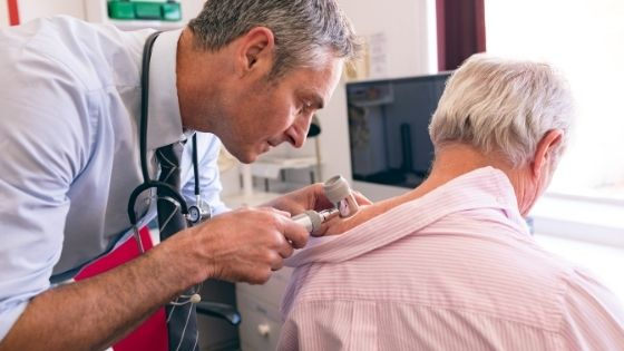 A doctor is seen inspecting a suspicious skin spot on a senior male's shoulder